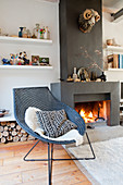 Wicker chair next to fire in open fireplace