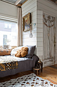 Couch next to rustic fitted cupboard made from reclaimed wooden boards