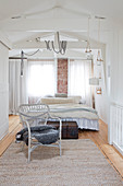 Korbstuhl mit Fell im hellen Schlafzimmer unter dem Dach