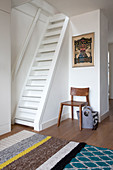 Chair next to steep stairs in the hallway with wool carpet