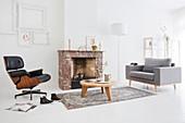 Klassiker Lounge Chair, Coffeetable und grauer Polstersessel vor Kamin in weißem Wohnzimmer