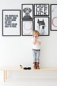 Little boy stood on wooden bench below black-and-white posters with mottoes on wall