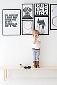 Junge steht auf Holzbank vor schwarz-weißen Botschaften an Wand