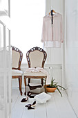 Antique upholstered chairs and ladies' clothing in bright room