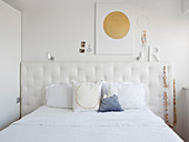 Scatter cushions on double bed with button-tufted headboard below decorations on wall