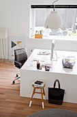 White designer desk and black swivel chair in study