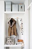 Winter jacket in white coat rack below boxes in niche