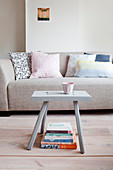 Scatter cushions on pale grey sofa and stool used as small table in living room