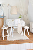 Various chairs and bench around table with white lace cover