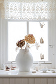 Vase of dried flowers on windowsill
