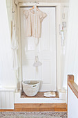 White door with a hanging blouse, basket, and shoes in front of it