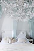 Weißes Doppelbett im Schlafzimmer mit hellblauen Balken, im Vordergrund romantische Lampe