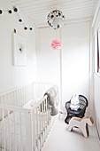 Gitterbett, Holzpferd und Kinderstuhl mit Hasenfigur in weißem Kinderzimmer