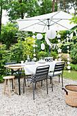 Gedeckter Tisch, Sonnenschirm und Partydeko in sommerlichem Garten