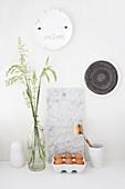 Gräser in Bügelflasche, Eier, Marmorbrett und Wandteller