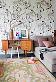 Retro desk with stool and couch against bird-patterned wallpaper