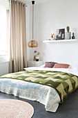 Green checked bedspread on double bed in bedroom