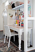 White desk and chair below colourful pictures on wall