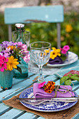 Set table decorated with summer flowers in garden