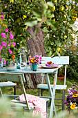 Flowers on set table below tree in summery garden