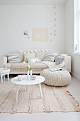 Couch, cushions, table and pouffe in festively decorated white living room