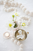 White wooden bead necklace, flowers and Christmas decorations on table