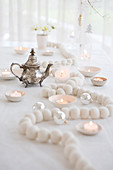 White wooden bead necklace, tealights and silver teapot on Christmas table