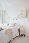Double bed in festively decorated, white bedrom