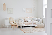Couch with scatter cushions, tables, pouffe and chair with sheepskin rug in festively decorated white living room
