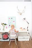 Mädchen sitzt an weißem Schreibtisch, Geweih und Papierdeko an der Wand