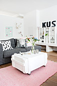White-painted trunk on castors used as coffee table, grey sofa and shelves in living room