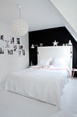 White double bed with headboard against black wall in bedroom