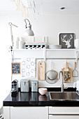 Kitchen utensils on and above black worksurface