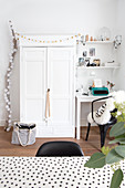 Festively decorated white cupboard between desk and chair and branch decorated with cotton ball fairy lights