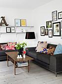 Graue Sofas mit verschieden gemusterten Kissen und Bildergalerie im Wohnzimmer