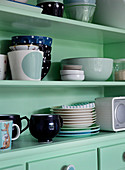 Various dishes on a mint green shelf
