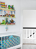 Shelves with toys above the cot in the children's room in white