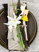 Daffodils, feathers, and twigs on fringed fabrics as table decorations