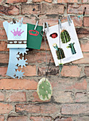 Paper crown, greeting card, and a leaf of a prickly pear on a string
