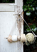 Balls of string on a rod hung from the door handle