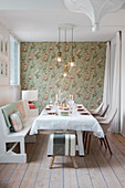 Festively set table, white bench and chairs in dining room with bird-patterned wallpaper