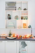 Cotton ball fairy lights on kitchen worksurface below ornaments on shelves