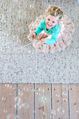 Soap bubbles above little girl wearing tutu and holding bead necklace on wool rug