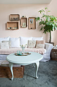 Round coffee table in front of sofa with lacy blanket and vintage-style accessories in living room