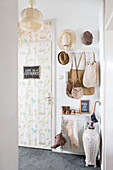 Vintage-style wallpaper on door and old-fashioned accessories in hallway