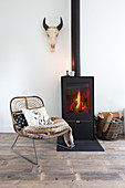 Rattan chair in front of the fireplace with a burning fire