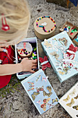 Child rummages in boxes of crafting materials on the beach