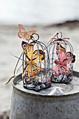Butterflies made of feathers and metal in small decorative cages