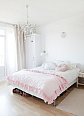 Pink ruffled blanket on the bed in the bedroom in white