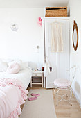 Pink ruffle blanket on the bed, wardrobe and chair in the bedroom in white